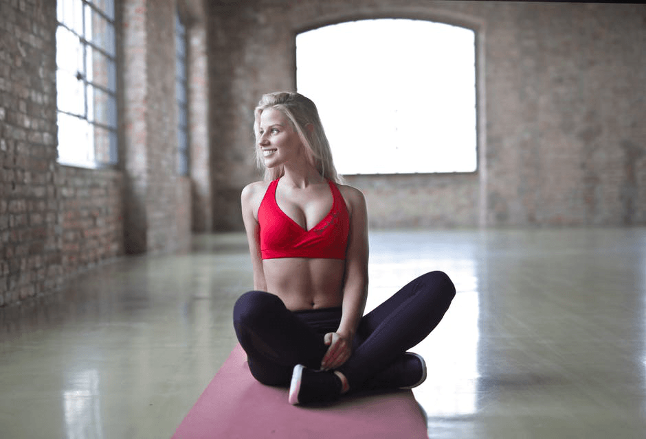An athletic woman wearing a red sports top sitting on a yoga mat
